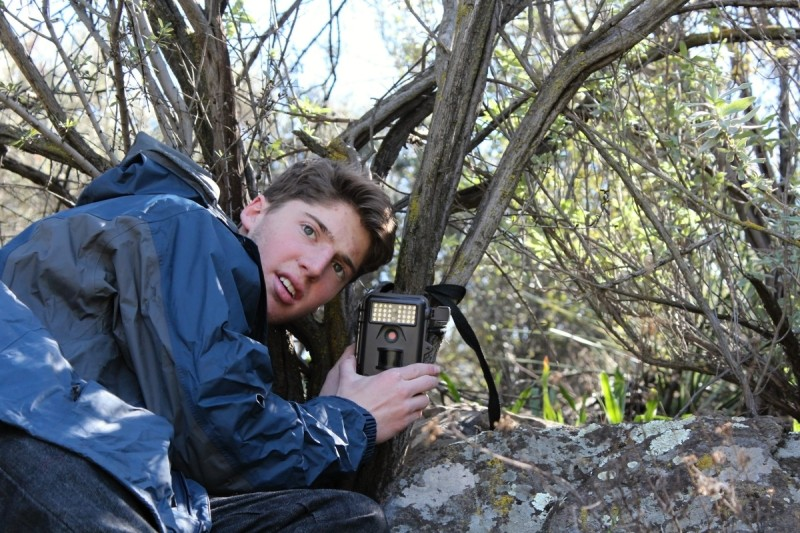 Camera Trappin' - Tanner Saul positions a camera - Photo courtesy of Saul